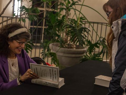 Shoshana Zuboff signs a student's copy of her book,